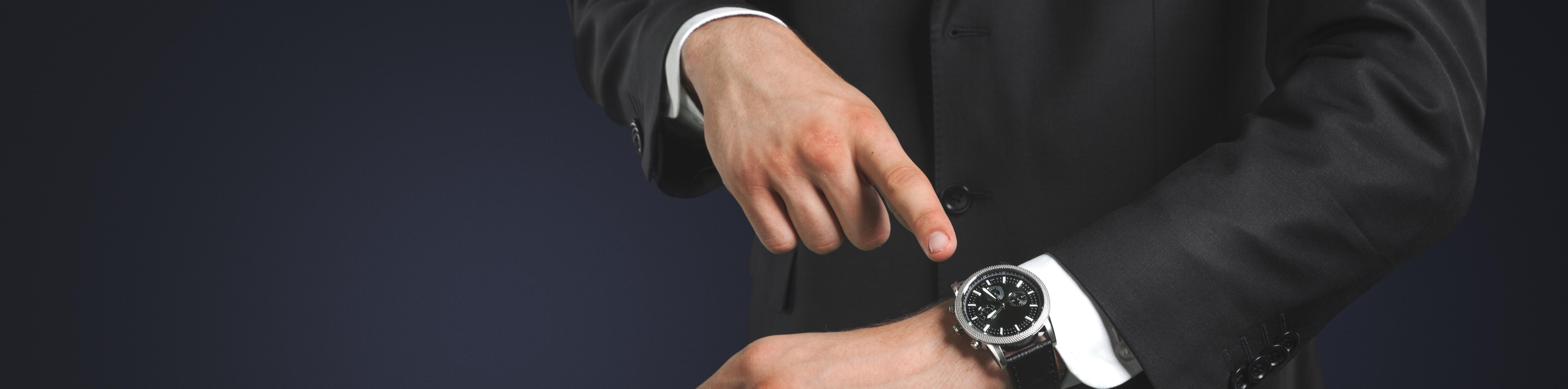 Kaufmann zeigt auf seine Armbanduhr
